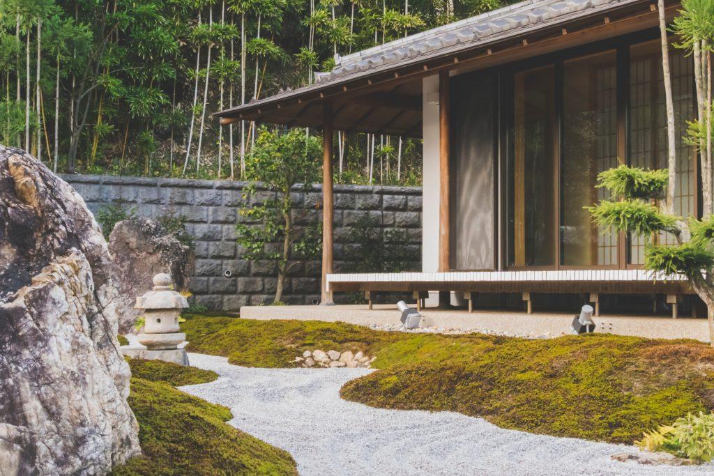 Jardin japonais devant une petite maison en baie vitrée