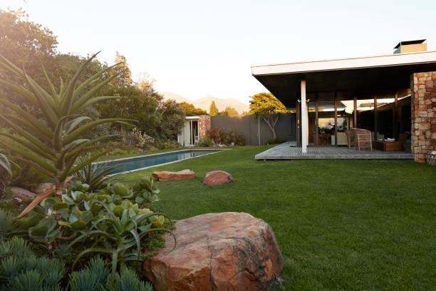 Grand jardin avec belle pelouse, piscine creusée, terrasse et pierres.