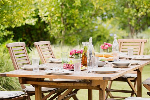Table de jardin bien dressée sous un arbre