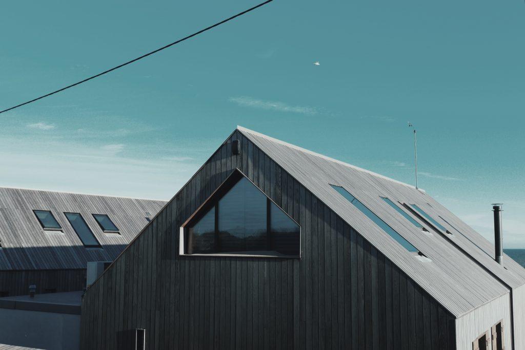 Un maison moderne grise avec un toit pentu