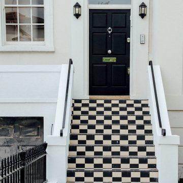 Porte d'entrée noire d'une maison moderne avec escalier noir et blanc