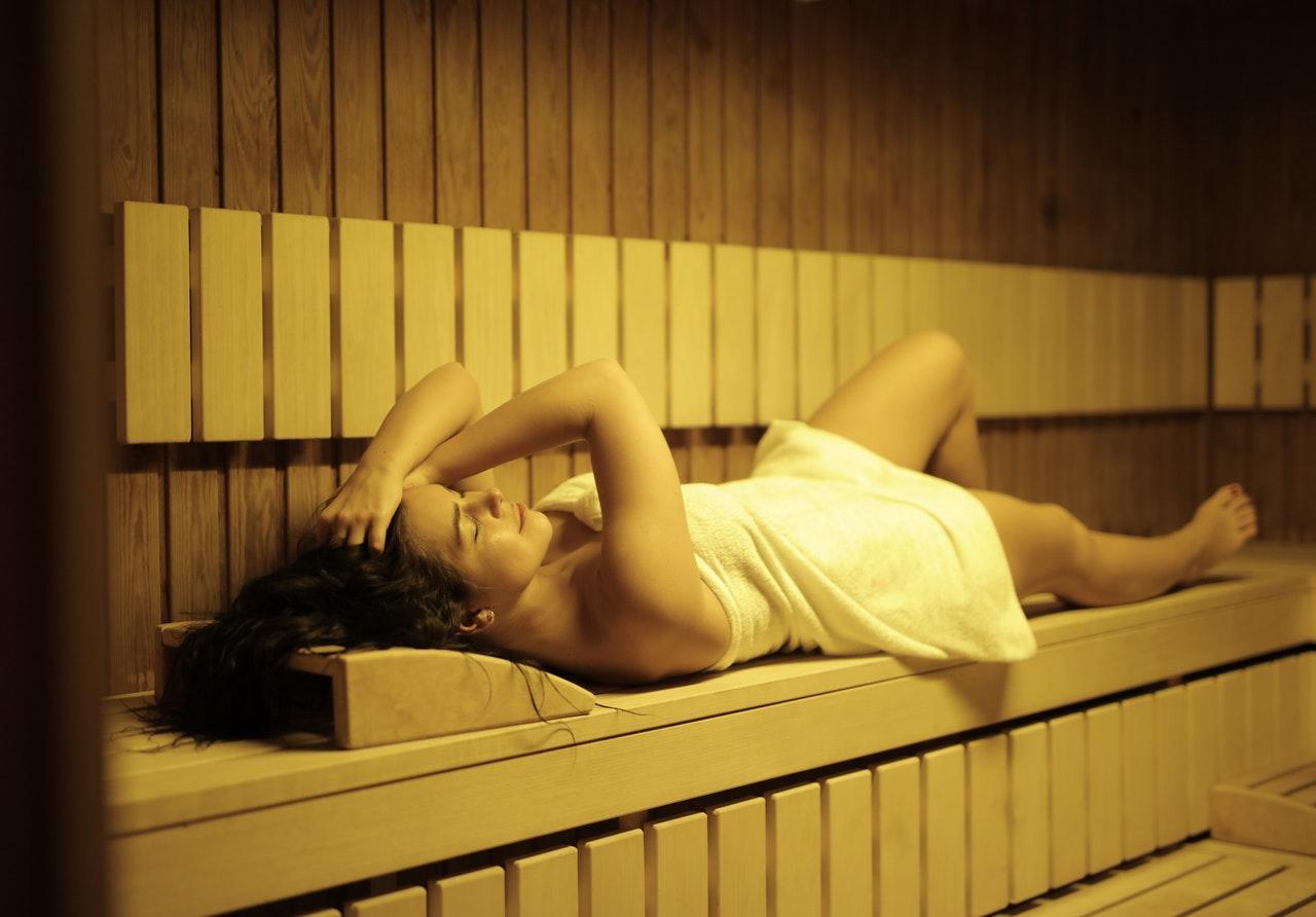 jeune femme allongée dans un hammam en bois